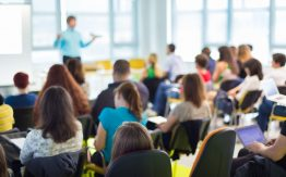 Teacher lecturing students in large classroom>