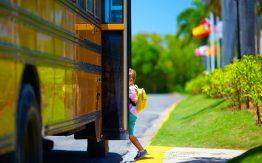 Kid getting on school bus>